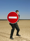 Businessman holding 'no entry' sign in desert, full length