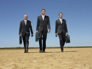 Three businessmen with briefcases walking through desert, full length