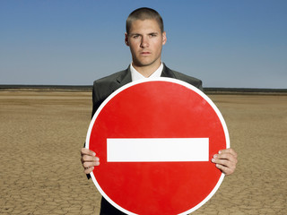 Businessman holding 'no entry' sign in desert, half length