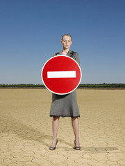 Businesswoman holding 'no entry' sign in desert, full length