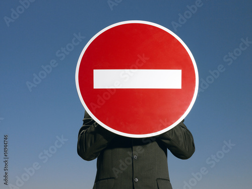 Man in suit holding 'no entry' sign in front of face, half length
