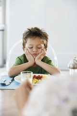 Young boy with head in hands at dinner table