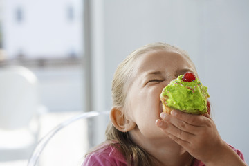 Young girl eating cupcake, head and shoulders