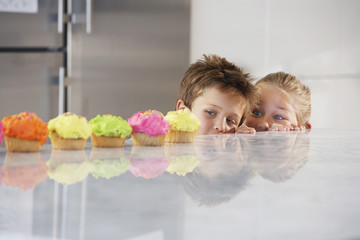 Young girl and boy peeking over counter at row of cupcakes, high section