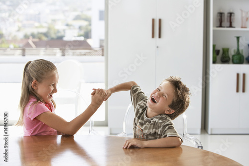 Young girl and boy fighting at table at home