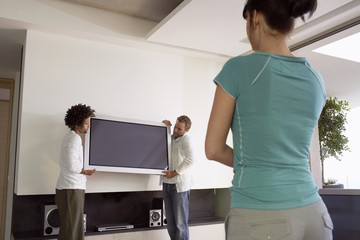 Young woman watching as two young men move plasma television, back view