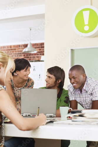 Four people having meeting around laptop.