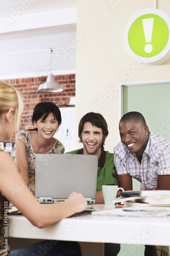 Four people having meeting around laptop, laughing.