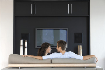 Couple sitting in front of flat screen television in living room, back view