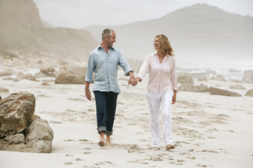 Couple walking on beach, holding hands