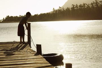 Boy 7-9 standing on dock, pulling in float tube.