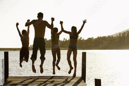 Rear view of father and children jumping off a pier holding hands