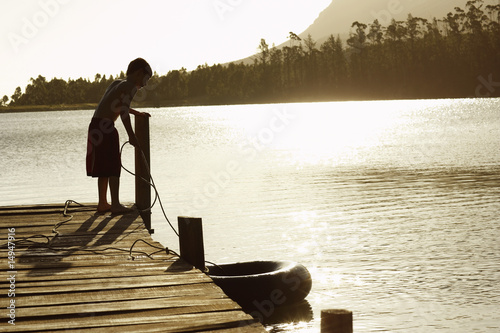 Boy 7-9 standing on dock, pulling in float tube.