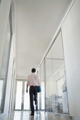 Businessman Walking in Corridor, low angle back view.