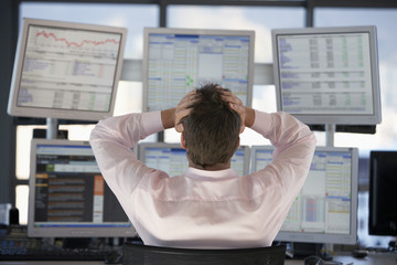 Businessman watching computer screens, with hands on head, back view.