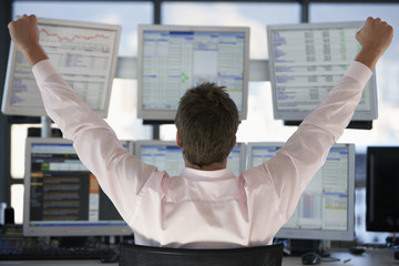 Businessman watching computer screens with arms raised, back view.