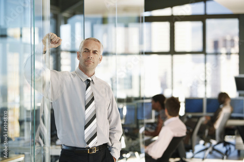 Businessman leaning on door in office, with office workers in background.