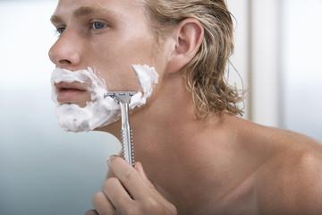 Man shaving face in bathroom, close-up