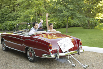 Mid adult bride and groom in vintage car, waving hands