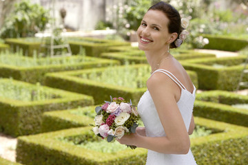 Mid adult bride in garden, holding bouquet, smiling