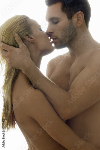 Naked couple embracing, studio shot