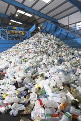 Used plastic bottles on conveyor belt in factory