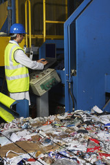 Man operating conveyor belt in recycling factory, side view