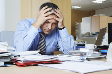 Businessman sitting at desk with head in hands