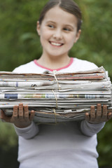 Girl 10-12 holding bundle of waste paper, smiling, looking away focus on pile