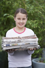 Girl 10-12 holding bundle of waste paper, smiling