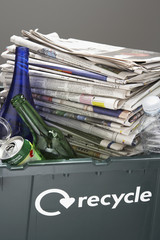 Recycling bin filled with waste paper and bottles, close-up