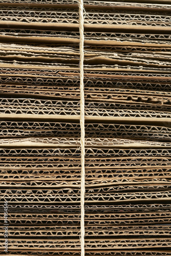 Bundle of corrugated cardboard tied with string, close-up, full frame