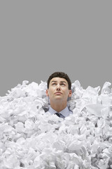Adult man covered in crumpled paper, looking up