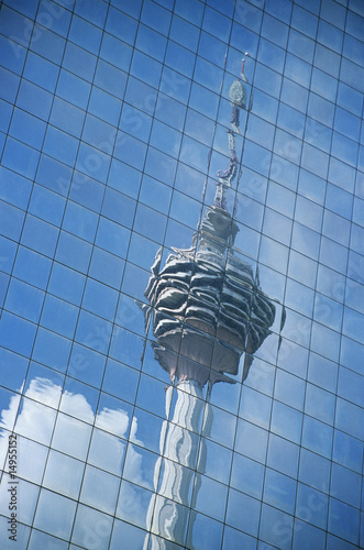 Distorted reflection of Kuala Lumpur Tower in building wall, full frame