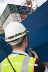 Man wearing hard hat using walkie-talkie at container terminal, back view