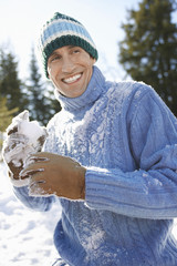 Man wearing winter clothing holding snowball, portrait