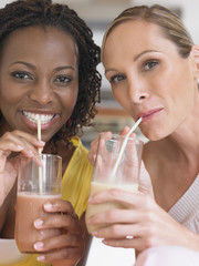 Two women drinking milkshake, portrait
