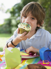 Portrait of young boy 10-12 eating cupcake at birthday party