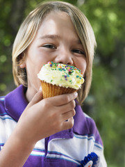 Portrait of young boy 7-9 eating cupcake