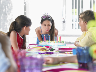 Girl 10-12 blowing out birthday candles at party