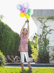 Portrait of girl 10-12 holding bunch of balloons over head