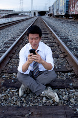 Asian man making call on train tracks