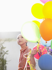 Girl 10-12 with bunch of balloons