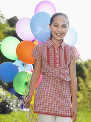 Portrait of girl 10-12 with bunch of balloons, smiling