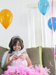 Young girl 7-9 on sofa preparing birthday balloons