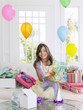 Portrait of young girl 7-9 with birthday presents, smiling