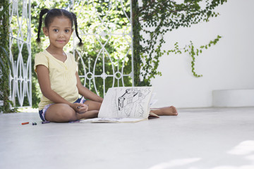 Girl 5-6 years sitting on porch and drawing