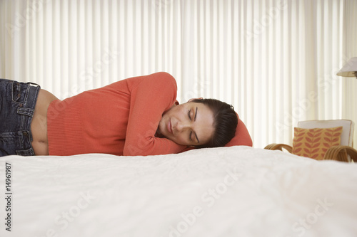 Mid-adult woman sleeping on bed