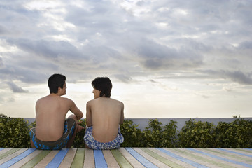Two teenage boys 16-17 sitting on wooden deck, back view