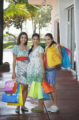 Three teenage girls 16-17 carrying shopping bags, standing on street, portrait